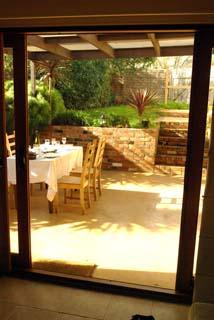 View through glass door into al fresco dining area and garden.