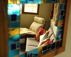 Lounge room reflected through wall mirror.